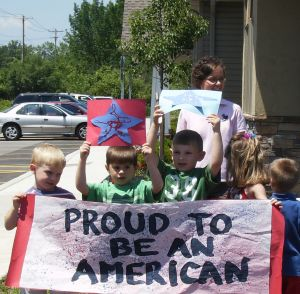 Local EduKids and staff display patriotic banners and signs while the traveling Vietnam Veterans Memorial makes its way to the Knox Farm State Park in East Aurora.